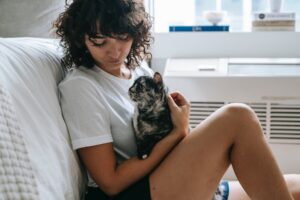 young woman embracing and caressing obedient cat at home