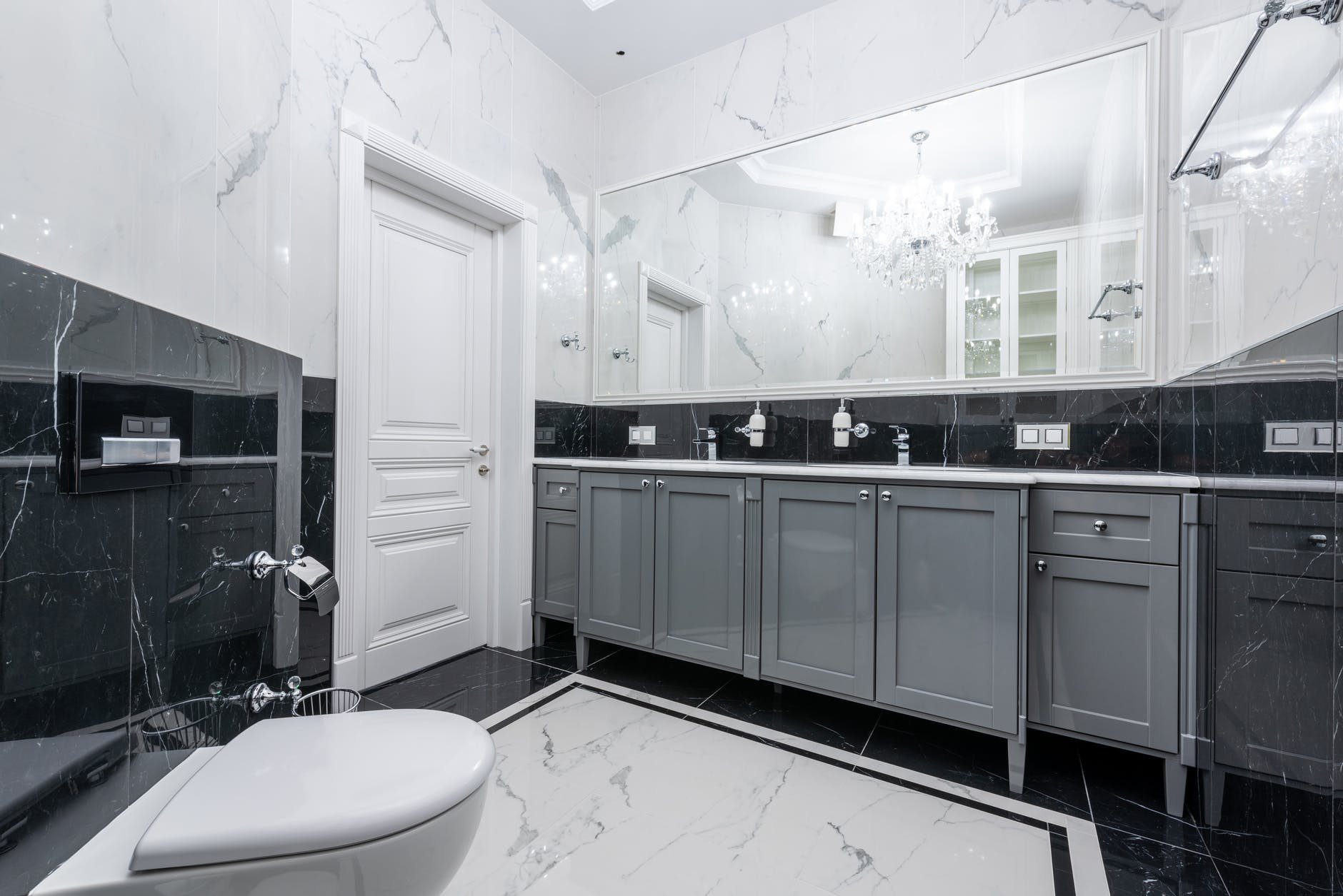 prestige bathroom with large mirror and glowing chandelier